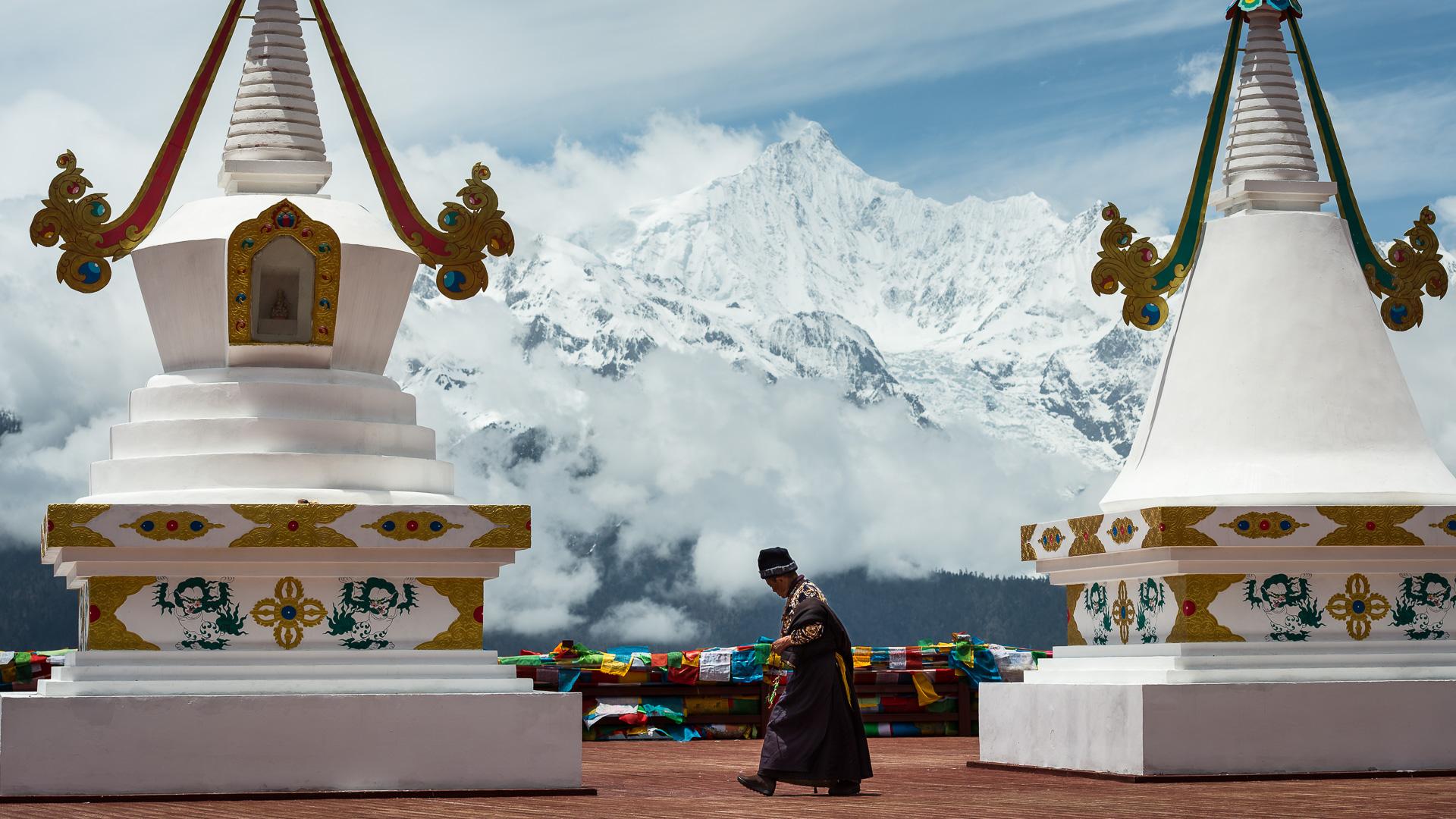 A Tibetan man prayer walks around stupas