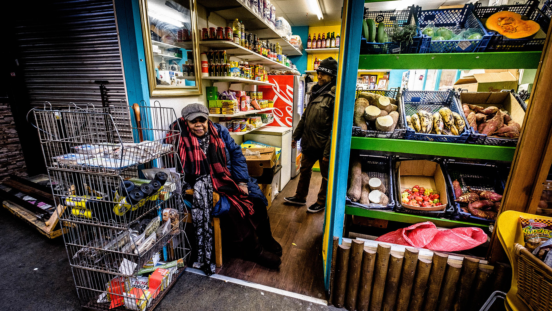 A Jamaican shopkeeper sits in front of her grocery store in London.