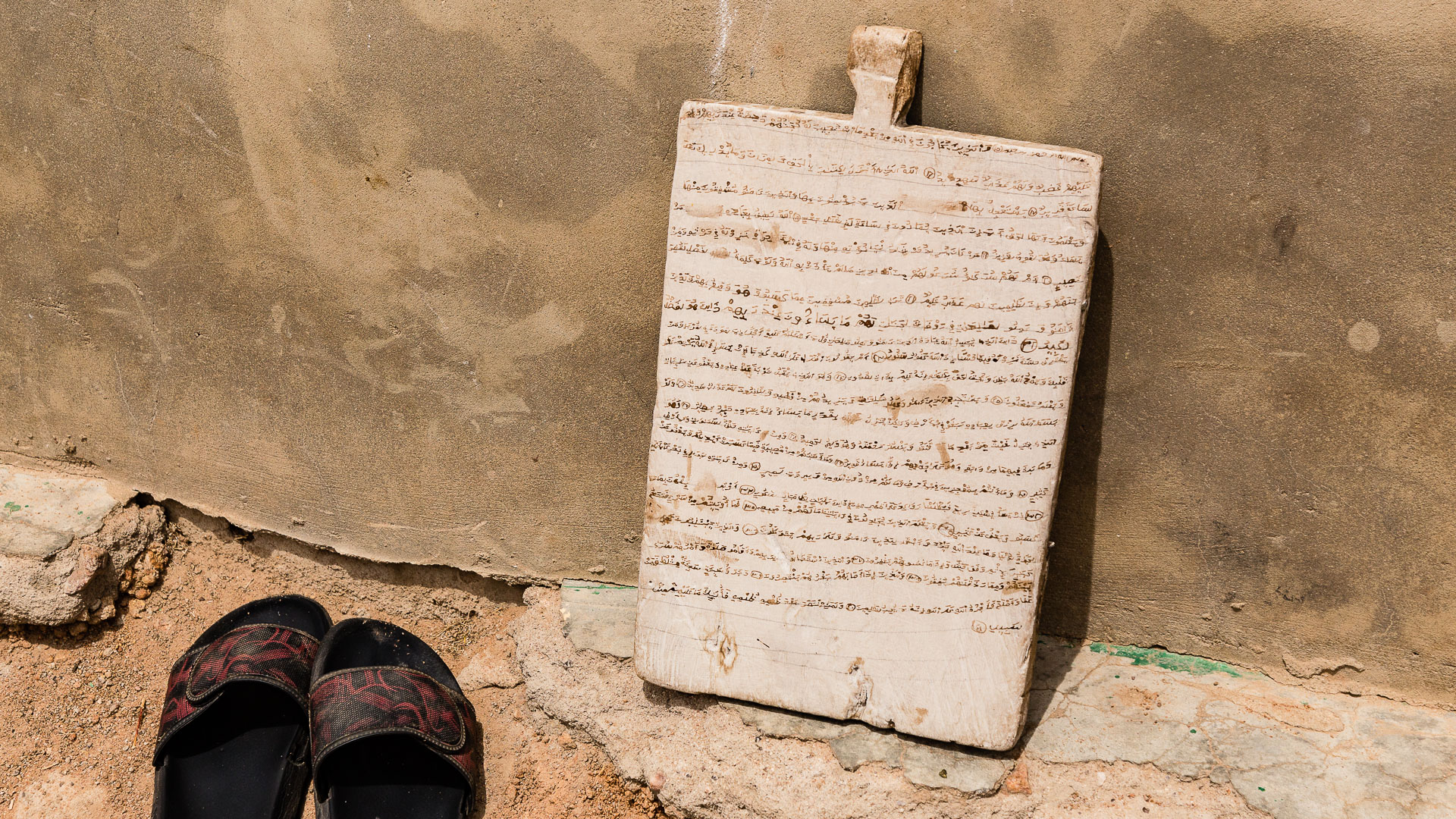 A wooden tablet used to practice writing and memorizing Qur'anic verses stands outside a mosque.
