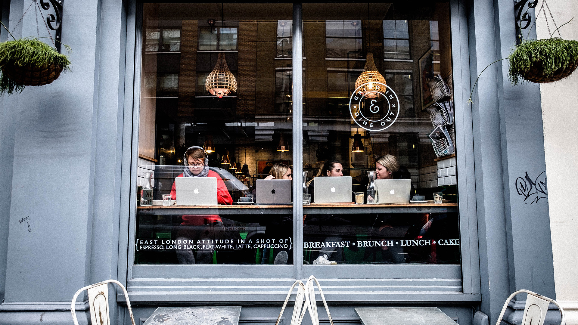 Women work on their laptops at a coffee shop in London.